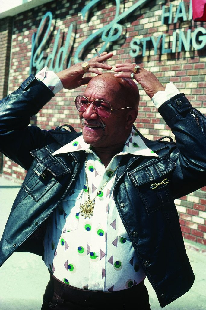 "The comedian Redd Foxx, best known for his role in the sitcom ""Sanford and Son,"" posing in front of the Redd Foxx Hair Salon in Los Angeles in an undated photograph. Mr. Foxx cofounded the shop with Roger Simon, a barber whose clients included Duke Ellington, Sugar Ray Robinson and Nat King Cole.CreditIsaac Sutton/Johnson Publishing Company"